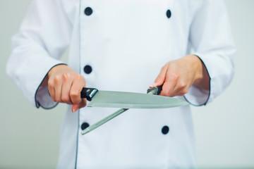 Female chef sharpening a knife Fototapete