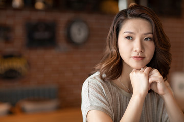 Elegant woman with hand on chin in cafe