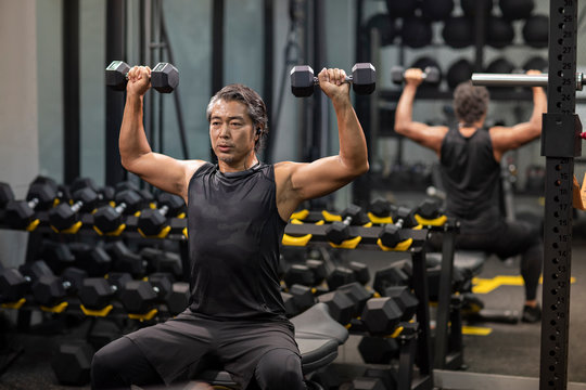 Mature man working out with hand weights at gym