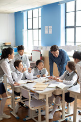 Teacher talking with students in classroom