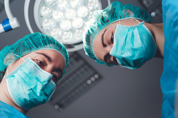 From below female surgeons in medical uniform using professional tools while standing under bright light in operating theater