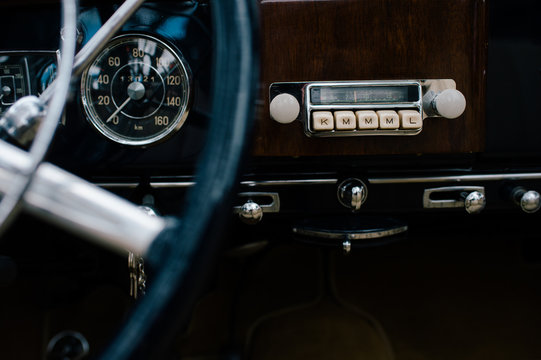 Fragment of metal steering wheel and dashboard of old classical automobile