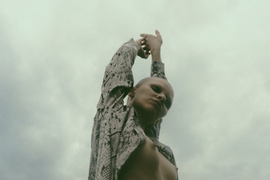 Stylish bald woman with bare breast against cloudy sky