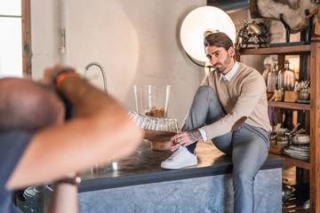 Unrecognizable man focusing and taking shot with camera of stylish adult guy in casual clothes looking away and contemplating while sitting with leg bent on wooden table against small window in light photo studio