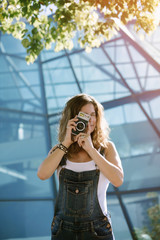 Young woman taking picture with camera in city
