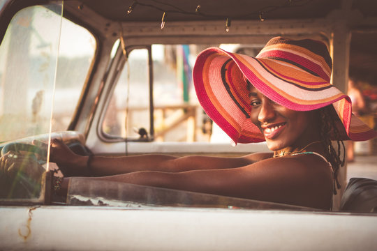 Side view of cheerful young African American female in colorful wide brimmed striped hat sitting behind wheel of vintage van and looking at camera