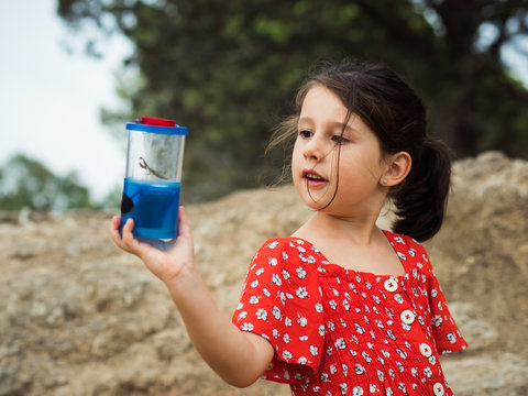 Little girl in red dress examining insect in jar on summer day in nature
