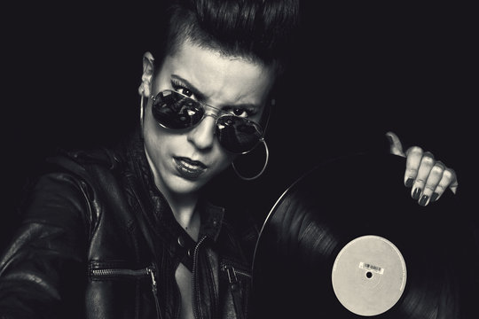 Angry confident female rocker in leather jacket and aviator sunglasses looking at camera and holding vinyl record in studio on black background