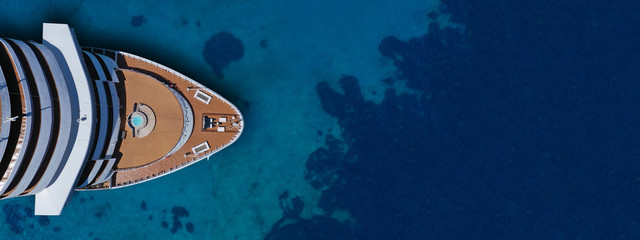 Aerial drone ultra wide photo of cruise liner nose cruising in Mediterranean Aegean deep blue sea