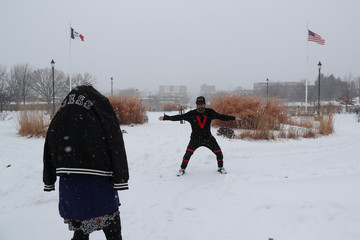 A dancer practices dance steps while recording a video at Des Moines Capitol area during a snowfall in Des Moines, Iowa,
