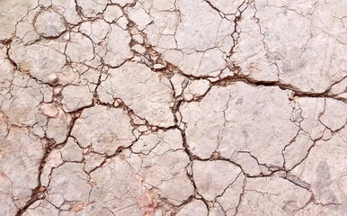 Broken soil or close-up damaged  ground. Photo of land in the desert. Cracked soil crust. Hard shadows and  dried soil from above. Royalty free stock images.