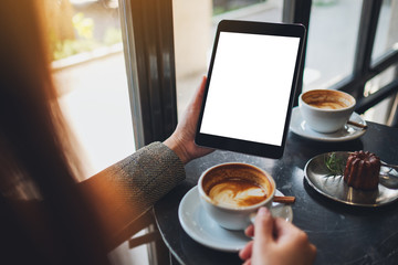 Mockup image of a woman sitting and holding black tablet pc with blank white desktop screen while drinking coffee in cafe