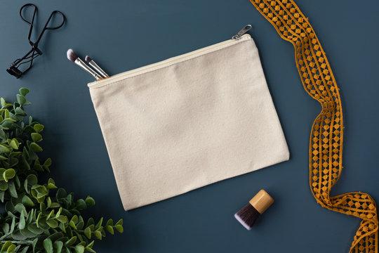 Plain blank canvas makeup zip case bag on a blue background mockup - makeup bag flat lay mockup