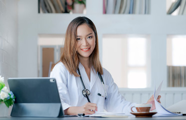Young female doctor working at office desk, smiling and looking at camera.