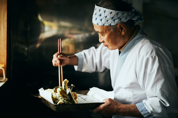 天ぷらを揚げる料理人