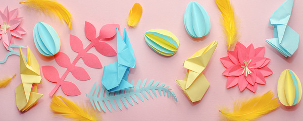 Easter holiday creative background with papercraft eggs, flowers, origami bunny on coral pink background, trendy paper craft holiday springtime background, banner, diy idea