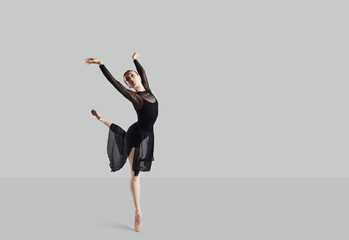 Woman ballet dancer over gray background.