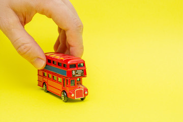 Foto op Aluminium Londen rode bus British toy double-decker red bus riding by male hand on yellow background. Concept of English language lesson and improving talking and speaking skills