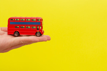 Printed roller blinds London red bus British toy double-decker red bus holding by male hand on yellow background with copy space for your text. Concept of English language lesson