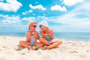 happy little girls eating watermelon at beach