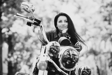 Sexy biker girl in a leather jacket is sitting on her motorcycle. Soft focus. Black and white photo. Close-up.