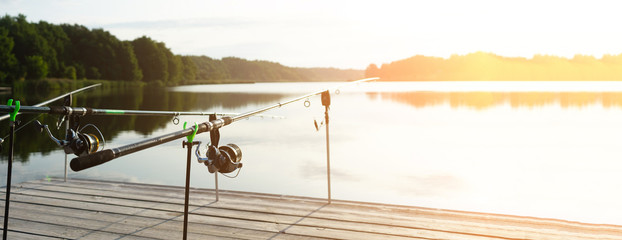 Carp fishing on beautiful blue lake with carp rods and rod pods in the summer morning. Fishing from the wooden platform.