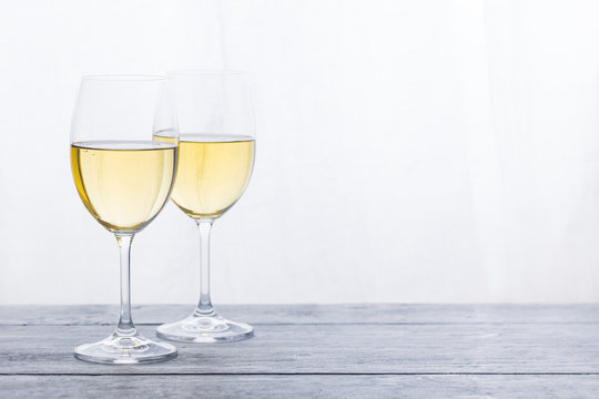 Two glasses with white wine on grey wooden background. Copy space.