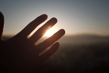 Closeup of a hand with the sun and hills on the blurry background
