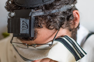 Close up, young jew men praying and a hand with tefillin and talit.
