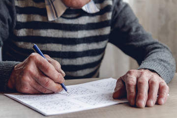 Senior solves sudoku or a crossword puzzle to slow the progressi