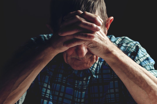 Depressed senior covers his face with his hands. Alzheimer's dis