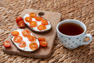 Delicious breakfast consisting of a cup of black tea and sandwiches with cottage cheese, fresh tomatoes and ground pepper. Selective focus, wicker wooden background. Healthy breakfast concept.