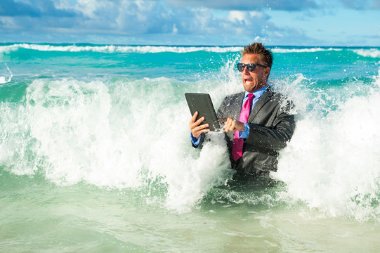 Fearful businessman using his tablet computer with oncoming waves crashing on the shore of a tropical beach