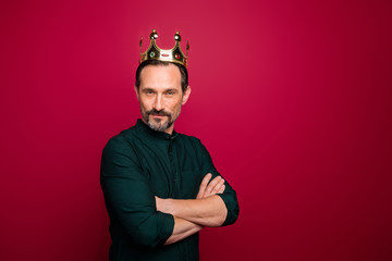 Turned photo of arrogant man looking at you with hands folded and crown on head isolated vivid color background