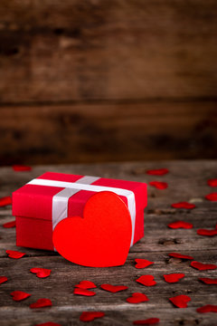 Valentine's day greeting card for love with red heart shape and gift box on wooden background