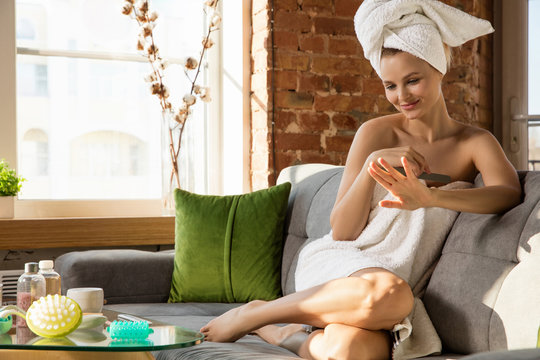 Beauty Day. Woman wearing towel doing her daily skincare and manicure routine at home. Sitting on sofa looks happy and calm. Concept of beauty, self-care, cosmetics, youth, home weekend, spa.
