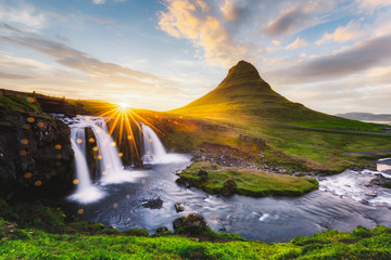 Morning landscape with rising sun on Kirkjufellsfoss waterfall and Kirkjufell mountain, Iceland,...