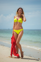 Very beautiful slim woman with a perfect figure stands and poses on a wild sandy beach