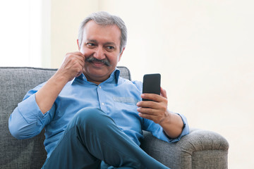 Portrait of a senior man sitting at home and doing a video chat on phone. Fotomurales