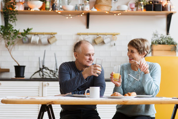 Portrait of relaxed fun senior couple together and eating breakfast in their kitchen at home