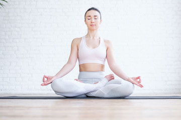 Healthy pacified young woman in tracksuit practices yoga in lotus position and mudra gesture on rug on floor on white brick wall. Healthy respiratory and nervous system concept. Advertising space