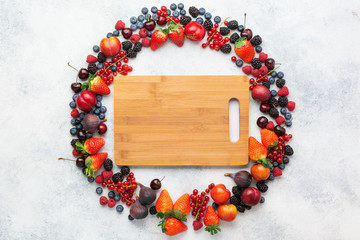 Wall Mural - Colorful berries background frame. Strawberries blueberries red currant blackberries raspberries, top view on white table, chopping board, copy space for text, selective focus