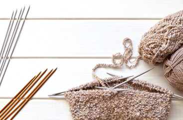 """Circular knitting for a warm """"bini"""" hat with five knit needles from boucle wool yarn and sets of knitting needles on a white wooden table. Copy space, flat lay, top view"""