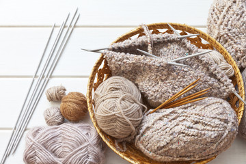 Needlework. Knitting a warm hat with five knitting needles from boucle wool and balls of woolen yarn in a wicker basket on a white wooden background. Flat lay, top view