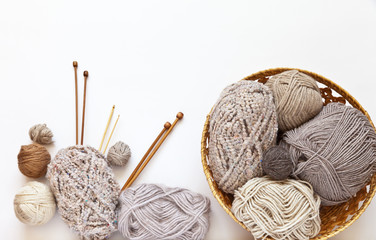 Balls of wool and boucle yarn in a wicker basket and different types of wooden knitting needles on a white background. Hand knit and crochet concept. Free space for text, flat lay, focus on clews