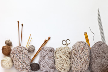 Accessories for hand knitting and balls of woolen yarn in beige colors on a white background. Hand knitting and needlework concept. Free space for text, flat lay, close-up, copy space, top view