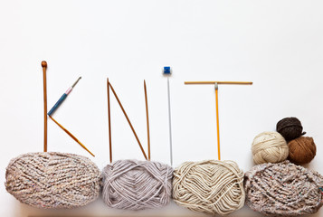 """The word """"knit"""" is written with knitting needles and hooks on balls of woolen yarn on a white background. Hand knitting and craft concept. Free space for text, flat lay"""