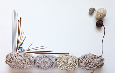 Balls of wool yarn in beige shades and different types of knitting needles on a white background. Hand knitting and hobby concept. Free space for text, flat lay, focus on clews