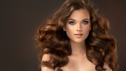 Poster Kapsalon Beauty brunette girl with long and shiny wavy black hair . Beautiful woman model with curly hairstyle .