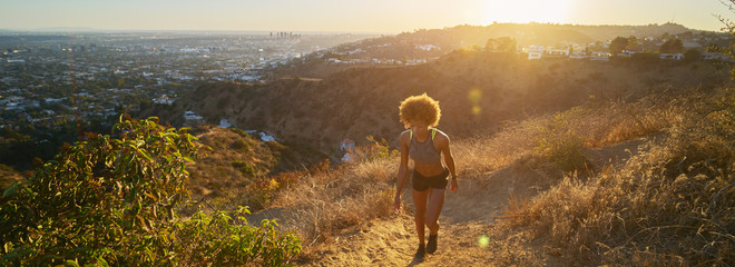 athletic african american woman hiking up runyon canyon trail at sunset